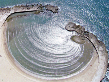 Arial shot of water waves diffracting through a gap